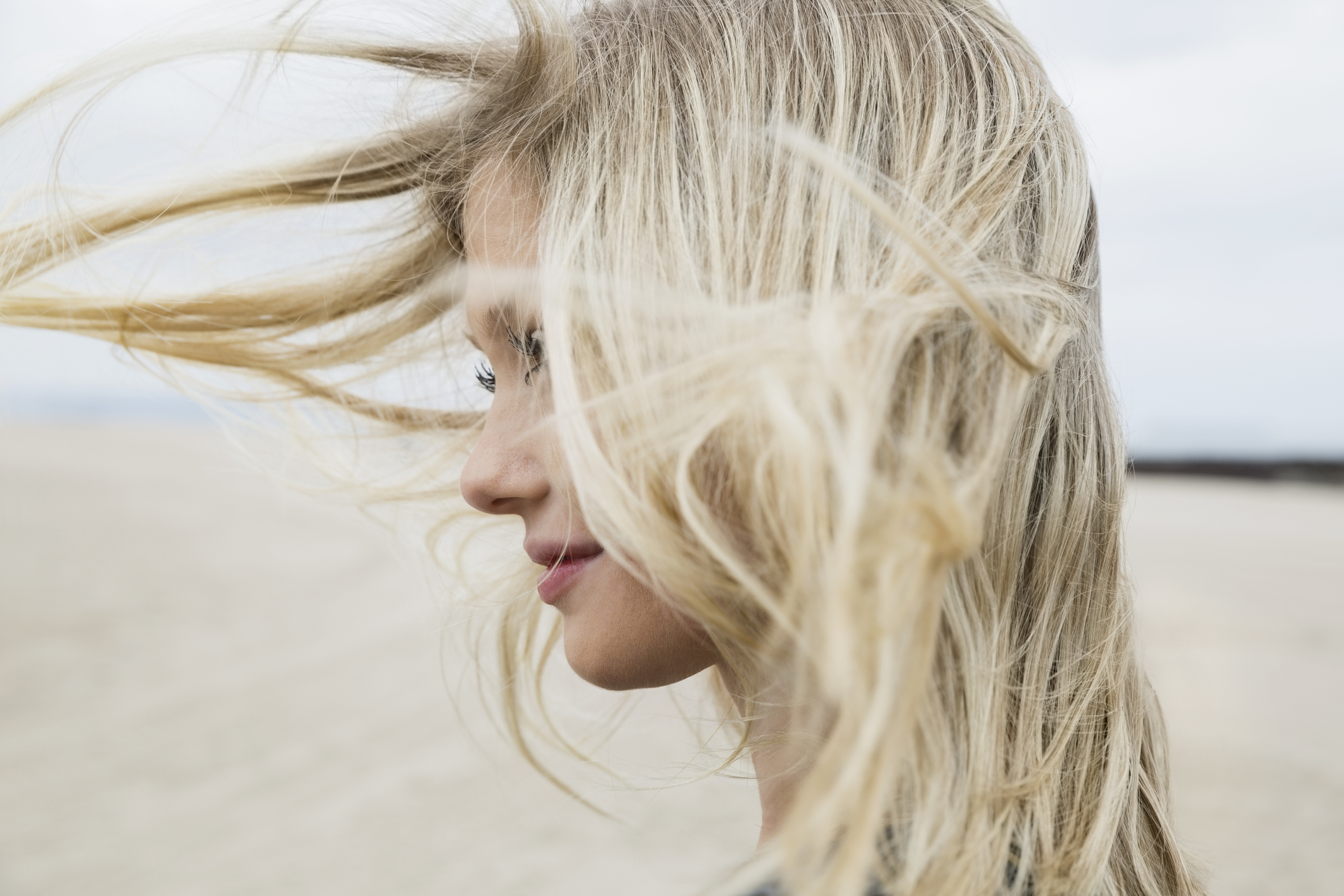 wind-blowing-blonde-hair-of-woman-at-beachjpg